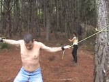 Outdoor bull whipping while tied in a tree by a domina