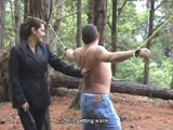 Bull whipping punishment to a tied man in the woods